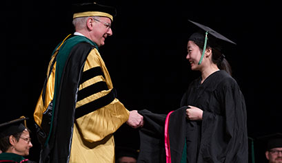 Dean Hess and student shake hands