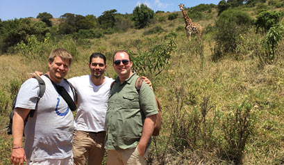 AMPATH travelers Dave Felker, Sylvain Demanze and Neil Flick stand in front of a giraffe in Kenya